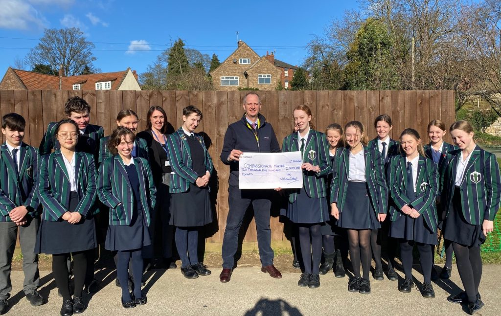 Witham's MD Nigel Bottom presenting a donation cheque to 'Compassionate Minster' and the children at Lincoln Minster School